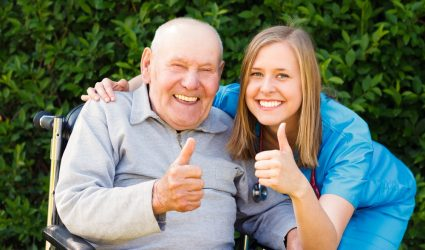 Happy smiling patient showing thumbs up together with his doctor.